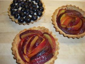 Mørdejsbunde med henholdsvis, marinerede nektariner og creme patisserie og blåbær.